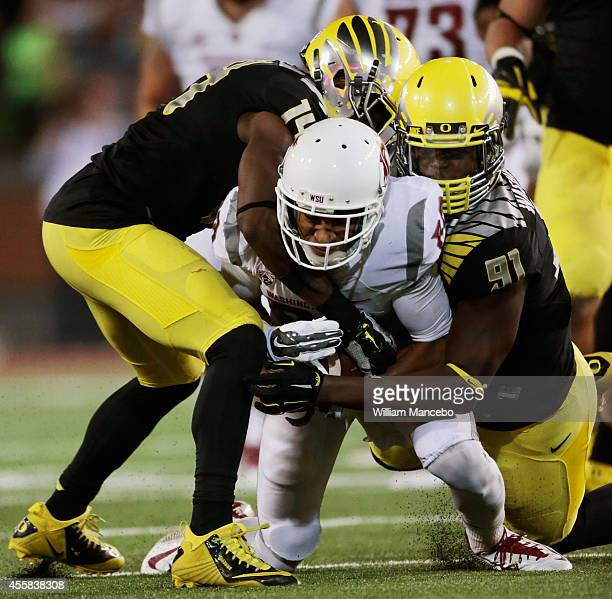 Isiah Myers of the Washington State Cougars is tackled by Ifo EkpreOlomu and Tony Washington of the Oregon Ducks during the game at Martin Stadium on...