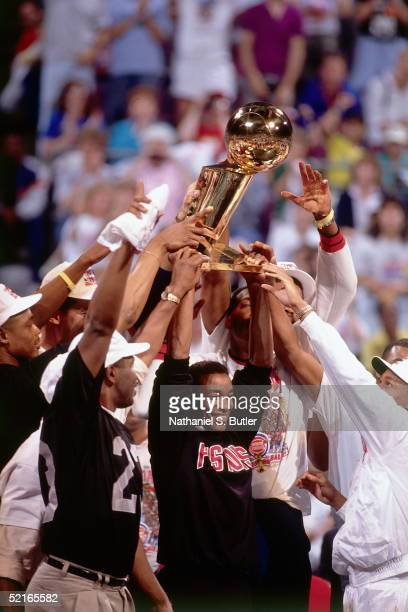 Isiah Thomas of the Detroit Pistons celebrates on the court with his teammates as they hold up the NBA Championship trophy after winning the Game...