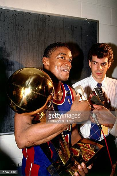Isiah Thomas of the Detroit Pistons celebrates with the Larry O'Brien trophy following there Game four victory over the Los Angeles Lakers to win the...