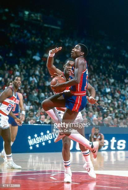 Isiah Thomas of the Detroit Pistons goes up for a layup on Rick Mahorn of the Washington Bullets during an NBA basketball game circa 1984 at The...