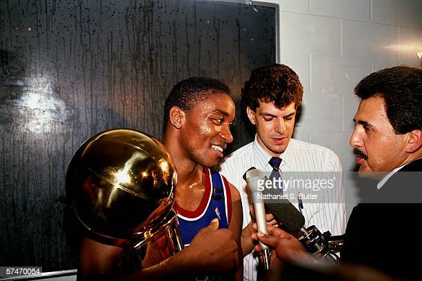 Isiah Thomas of the Detroit Pistons holds the Larry O'Brien trophy while being interviewed by reporters The Detroit Pistons defeated the Los Angeles...
