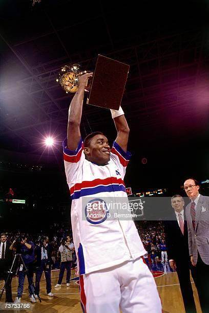 Isiah Thomas of the Detroit Pistons holds the Larry O'Brien Trophy up after the Pistons won the 1989 NBA Championship in Detroit Michigan NOTE TO...