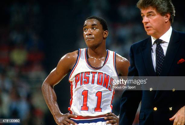 Isiah Thomas of the Detroit Pistons looks on with head coach Chuck Daly whiles there's a break in the action during an NBA basketball game circa 1987...