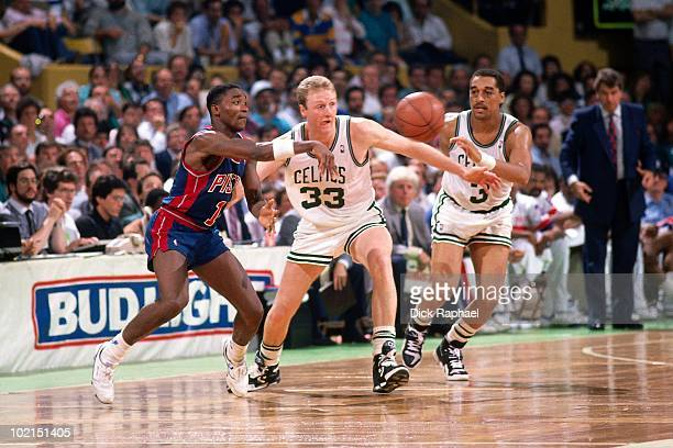 Isiah Thomas of the Detroit Pistons passes against Larry Bird and Dennis Johnson of the Boston Celtics during a game played in 1990 at the Boston...