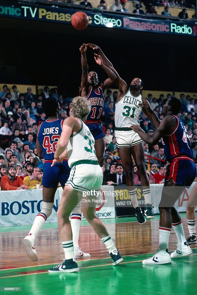 Isiah Thomas #11 of the Detroit Pistons shoots a jump shot against Cedric Maxwell #31 and Larry Bird #33 of the Boston Celtics during a game played in 1983 at the Boston Garden in Boston, Massachusetts.