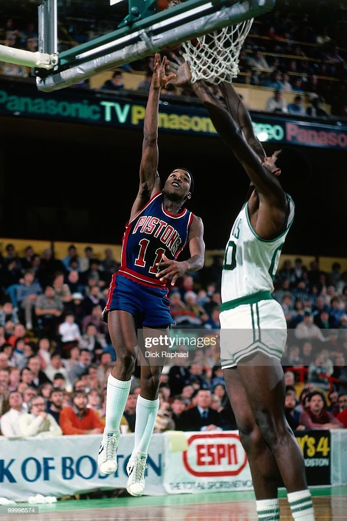 Isiah Thomas #11 of the Detroit Pistons shoots a layup against Robert Parish #00 of the Boston Celtics during a game played in 1983 at the Boston Garden in Boston, Massachusetts.