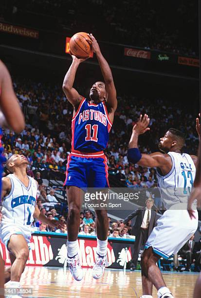 Isiah Thomas of the Detroit Pistons shoots over Muggsy Bogues and Kendall Gill of the Charlotte Hornets during an NBA basketball game circa 1992 at...