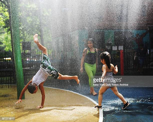Isiah Velez Mya Matos Isabela Pulla and Jordan Klipacki left to right play in the warter fountains at the Lillian Wald Houses in the East Village