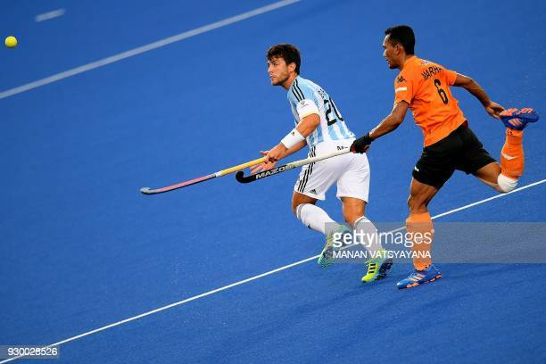 Isidoro Ibarra of Argentina challenges Malaysia's Marhan Jalil during their men's field hockey thirdfourth place match of the 2018 Sultan Azlan Shah...