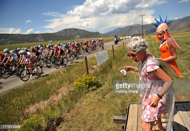 Isiri Hudhes front and Sarah Vick cheer the pack of cyclist during 606 mi first stage of 2013 USA Pro Challenge race in Aspen Colorado August 19 2013...