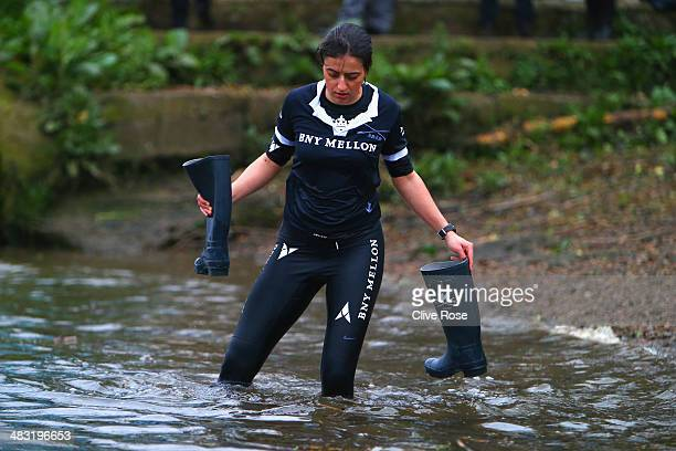 Isis Cox Sophie Shawdon retrieves her wellie boots after she was thrown into the Thames river by her crew competes during the BNY Mellon 160th Oxford...