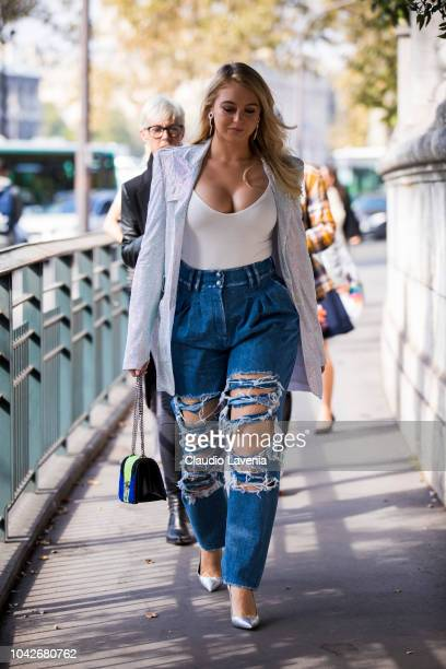 Iskra Lawrence wearing a white top shiny blazer ripped jeans silver heels and blue and green bag is seen before the Balmain show on September 28 2018...