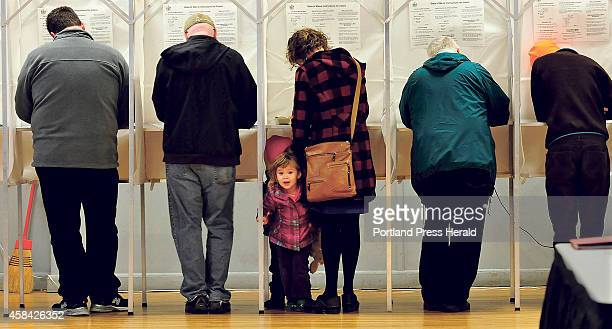 Isla Klepach peers out from a voting booth as her mother Denise casts her ballots on Tuesday Election Day in Waterville