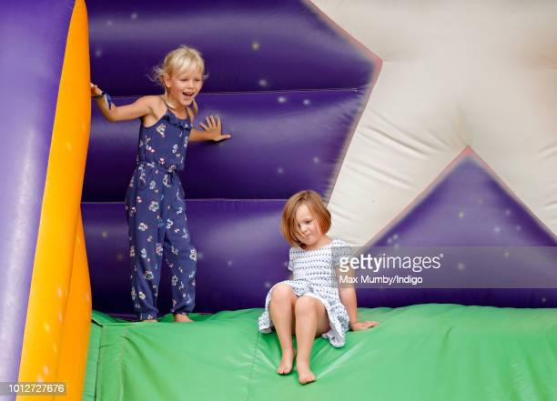 Isla Phillips and cousin Mia Tindall play on an inflatable bouncy slide as they attend day 1 of The Festival of British Eventing at Gatcombe Park on...