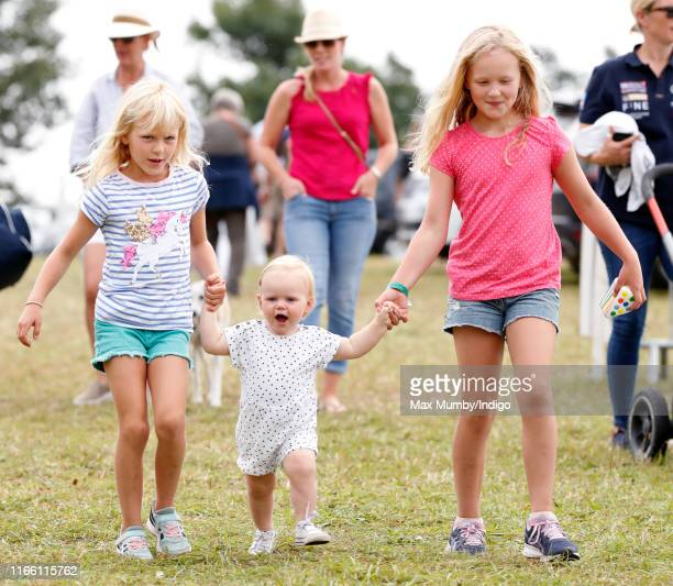 Isla Phillips and Savannah Phillips walk holding hands with their cousin Lena Tindall as they attend day 3 of the 2019 Festival of British Eventing...