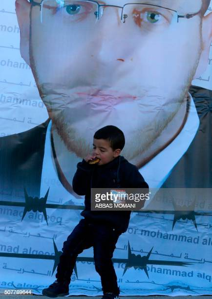 Islam plays in front of a giant poster bearing a portrait of his father Palestinian imprisoned journalist Mohammed alQiq during a press conference on...