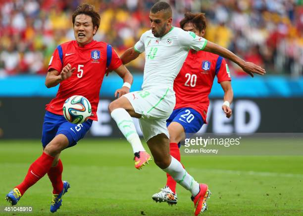 Islam Slimani of Algeria scores his team's first goal against Kim YoungGwon and Hong JeongHo of South Korea during the 2014 FIFA World Cup Brazil...