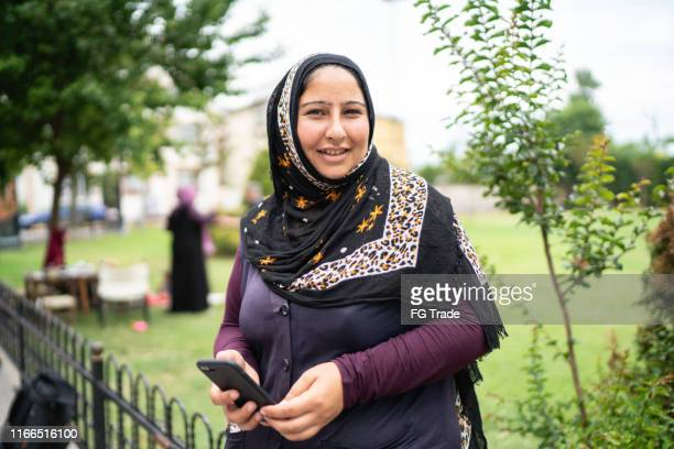 islam syrian woman using mobile portrait - syria stock pictures, royalty-free photos & images
