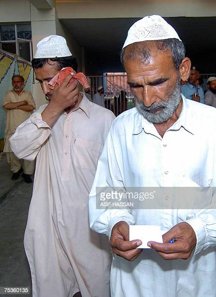 A freed Pakistani religious student of the Red Mosque weeps as he walks with his father following his release from the Adiala jail where he was...
