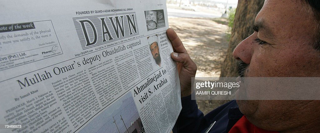 A Pakistani man reads a newspaper with headlines about the