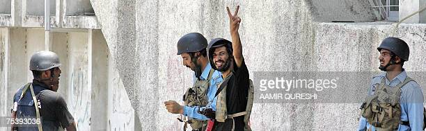 A Pakistani police commando flash victory sign as he takes position with his colleagues near the Red Mosque during a heavy exchange of fire in...