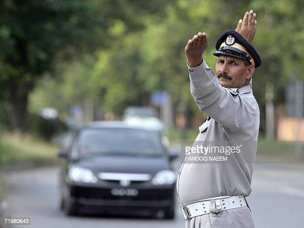 Pakistani policeman directs traffic after a major breakdown in traffic lights in Islamabad, 24 September 2006. Supply of electricity was disrupted...