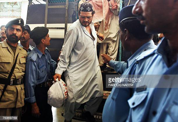 Detained Pakistani religious students of the Red Mosque come out of a police van as they arrive from the Adiala jail where they were locked following...