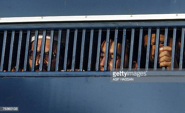Detained Pakistani religious students of the Red Mosque look out from a prisoner van as they arrive from the Adiala jail where they were locked...