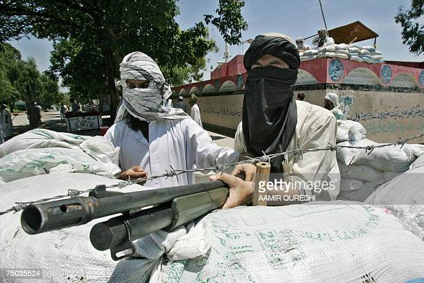 Masked Pakistani radical students of The Red Mosque take positon in a bunker outside the mosque during an exchange of fire between radical students...