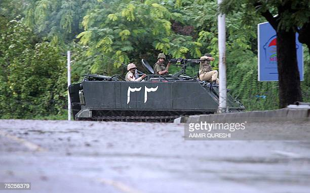 Pakistani army soldiers sit on an Armoured Personnel Carrier as they patrol near the radical Islamic Red Mosque during a heavy exchange of fire...