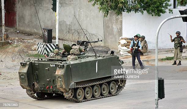 Pakistani army troopers sit on the top of an Armoured Personnel Carrier moving towards the besieged radical Islamic Red Mosque during a military...