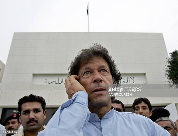 Pakistani cricketer turned politician Imran Khan talks on a cellular telephone as he stands in front of Parliament house in Islamabad, 23 August...