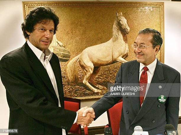 Pakistani former cricketer turned politician Imran Khan shakes hands with former Malaysian premier Mahathir Mohamad after a press conference in...