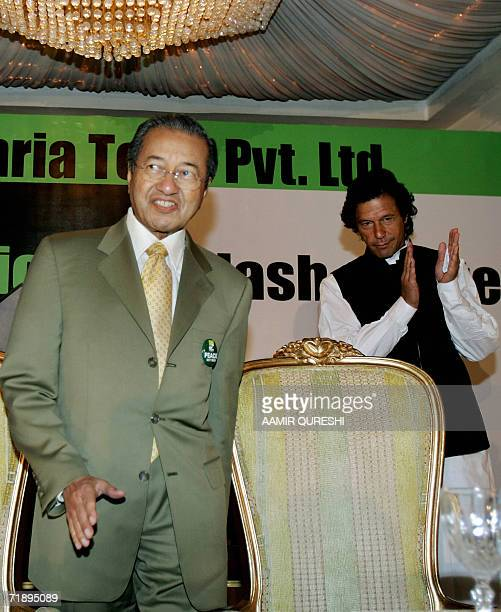Pakistani former cricketer turned politician Imran Khan applauds as Malaysian former premier Mahathir Mohammad prepares to address a seminar in...