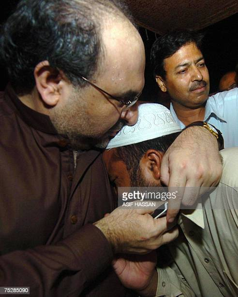 Pakistani Information Minister Mohammad Ali Durrani hugs with a relative of a religious student who is inside the Red Mosque after holding talks with...