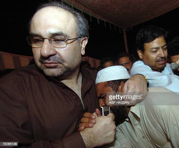 Pakistani Information Minister Mohammad Ali Durrani hugs with a relative of religious student who is inside the Red Mosque after holding talks with...