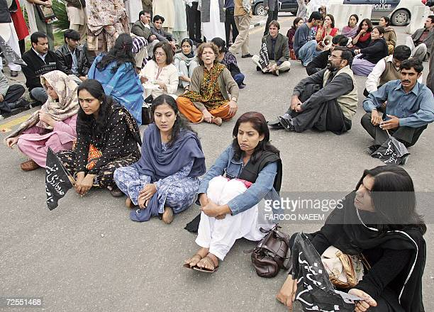 Pakistani NGO activists sit in protest outside the parliament building during a national assembly debate on rape laws in Islamabad 15 November 2006...