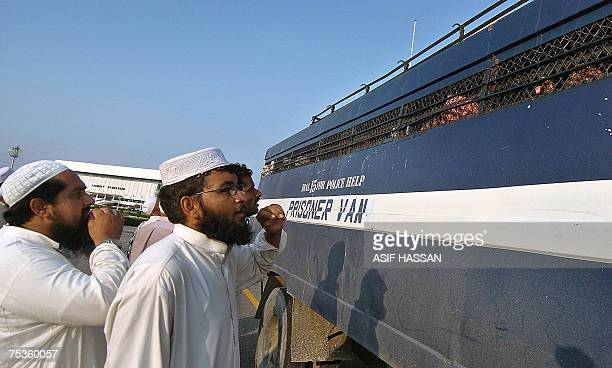 Relatives of Pakistani religious students of the Red Mosque talk with detained students sitting in a prisoner van as they arrive from the Adiala jail...