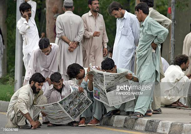 Relatives of Pakistani students of The Red Mosque browse through newspapers as they sit on a street in Islamabad 04 July 2007 reading details of the...