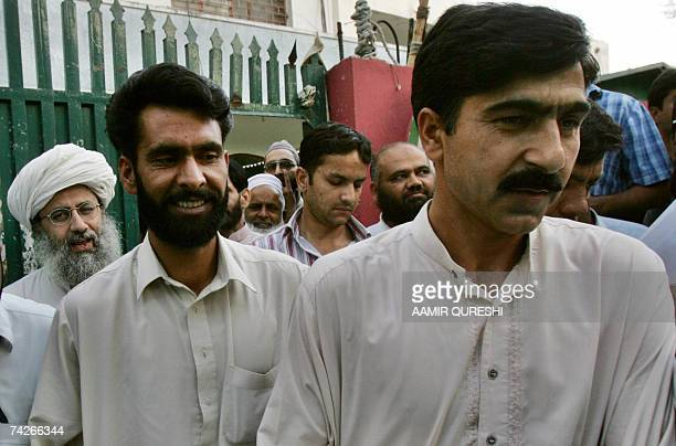Two Pakistani policemen leave the Red Mosque after their release as deputy leader of the mosque Abdul Rashid Ghazi looks on in Islamabad 24 May 2007...