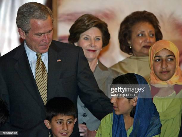 US President George W Bush talks with Pakistani earthquake survivors as US First Lady Laura Bush and Pakistani First Lady Sehba Musharraf look on at...