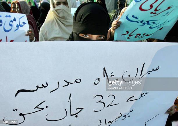 Veiled women activists of Pakistan's fundamentalist Islamic party of JamaatiIslami party carry placards during a demonstration in Islamabad 20 June...