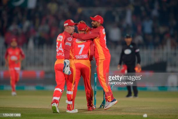 Islamabad United Asif Ali and Luke Ronchi celebrate with Shadab Khan after he successfully runs out Karachi Kings Babar Azam during the Pakistan...