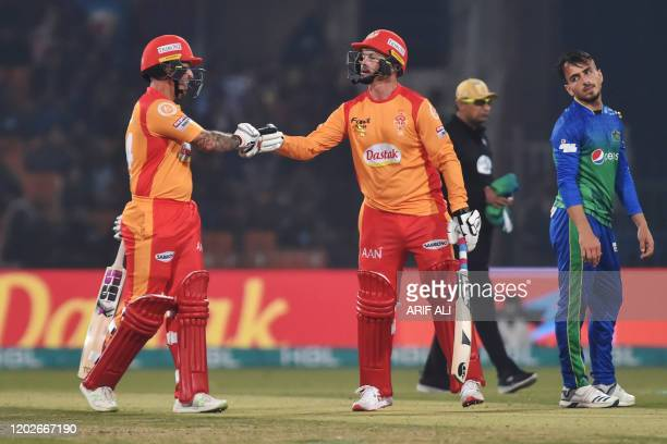 Islamabad United cricketer Luke Ronchi celebrates a half century with teammate Colin Munro during the Pakistan Super League T20 cricket match...
