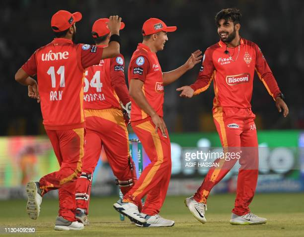 Islamabad United cricketer Shadab Khan celebrates with teammates after taking a wicket during the elimination match between the Islamabad United and...