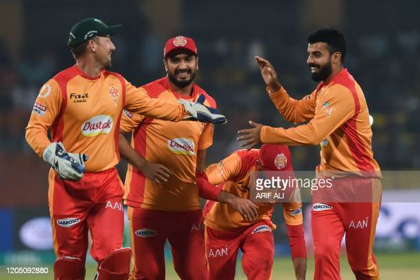Islamabad United's skipper Shadab Khan celebrates with teammates after the dismissal of Lahore Qalandars's Samit Patel during the Pakistan Super...