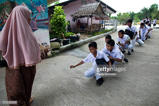 Islamic boys are told to walk like a duck as a punishment for being late to school at the Darunsat Wittaya school on August 16 2011 in Saiburi...