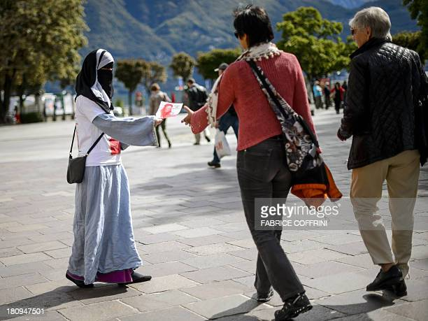 Islamic Central Council of Switzerland member Nora Illi one of the few Swiss women wearing the niqab distributes flyers in Lugano against an upcoming...
