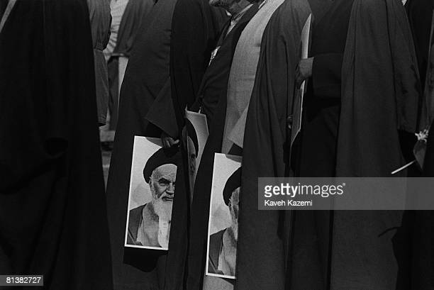 Islamic clergymen carrying pictures of Ayatollah Ruhollah Khomeini during the third anniversary of the Iranian Revolution 11th February 1982