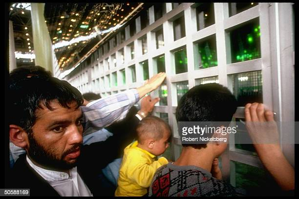 Islamic faithful visiting Ayatollah Khomeini's tomb peering through grills into rm containing only simple casket